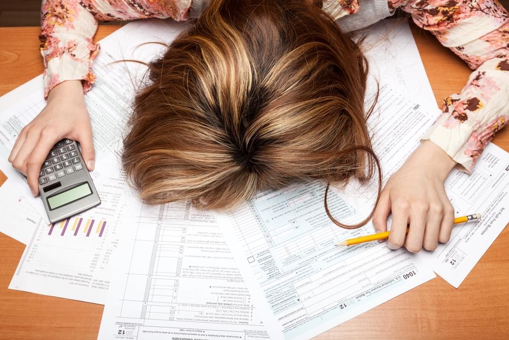 Eine Frau liegt mit dem Kopf auf dem Tisch voller Steuerunterlagen und hält einen Bleistift in der einen sowie einen Taschenrechner in der anderen Hand
