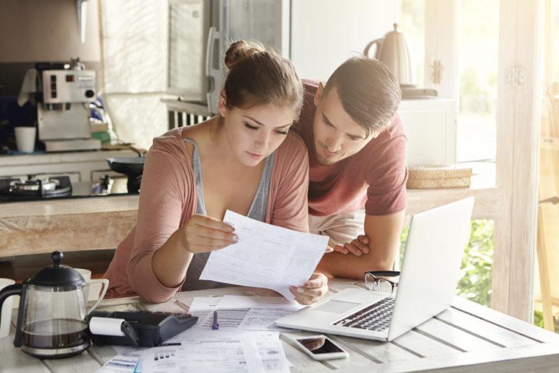 Ein junges Paar beschäftigt sich gemeinsam in der Küche mit den Finanzen und arbeitet mit einem Taschenrechner und einem Laptop